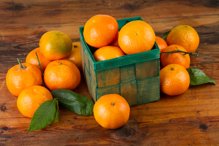 clementines: tangerine mandarin orange fruits in green box on old wooden table