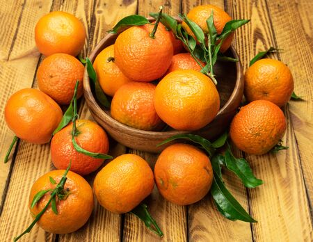 ripe organic mandarin fruits in wooden bowl over old wooden background