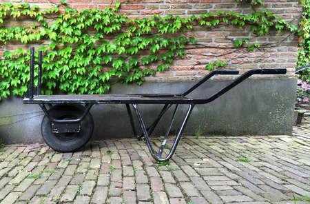 carretilla: Metal viejo negro carretilla holandesa en frente de hojas de hiedra y una pared de ladrillo con el espacio para el texto. Foto de archivo