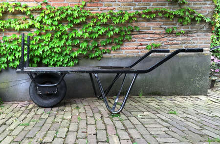 Old black metal Dutch wheelbarrow in front of ivy leaves and a brick wall with space for text.