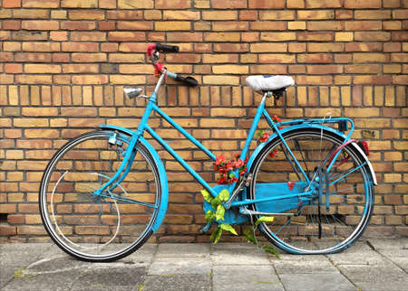 Ladies blue Dutch bicycle decorated with coloured flowers and leaves, resting against a brick wall.