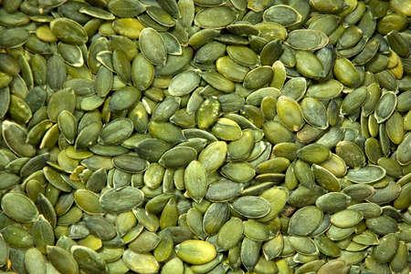 A background texture of green pumpkin seeds.