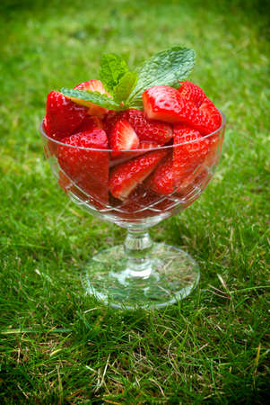 Red strawberries in a glass bowl on green grass.