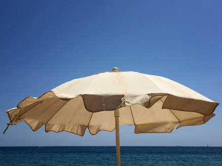 Sun umbrella blowing in the wind on a sunny day with the blue sky and sea in the background. Swimmers and a sailing boat in the sea. Space for text.