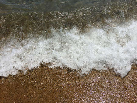 Closeup of a wave in the sea. The water and foam are flowing over the sand. With space for text.