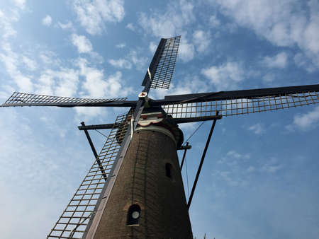 Windmill close up with a blue sky with clouds background on a sunny day. Space for text.