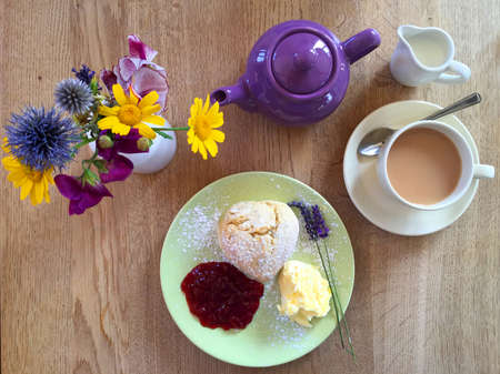 Traditional English afternoon cream tea with a scone, clotted cream, strawberry jam, a purple teapot, a cup of tea, a vase with flowers and some lavender on a wooden table.