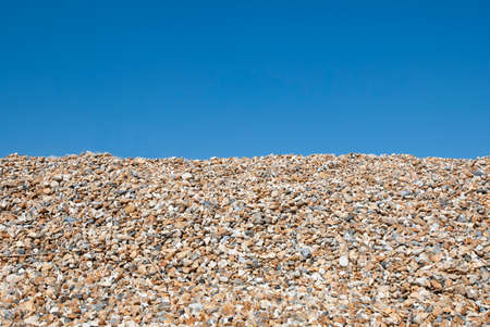 Pebbles on the beach on a sunny day with a blue sky in the background. Space for text.
