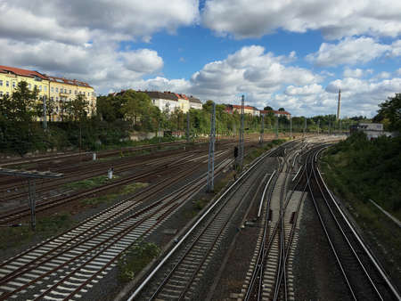 Railway tracks on a sunny day in the former East Berlin. Buildings on the side of the tracks. Space for text.