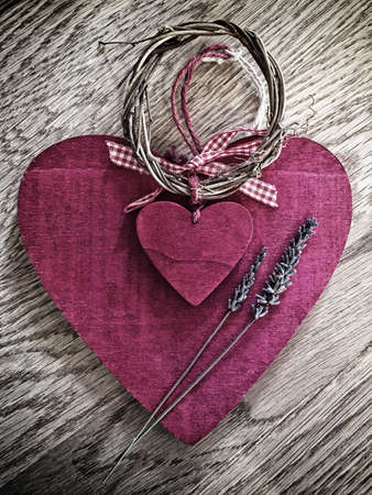 Two vintage wooden pink hearts tied with willow and checked ribbon with lavender sprigs on them on a wooden background. With a vignette and space for text.