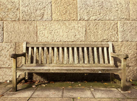Empty bench in front of a stone wall with space for text.