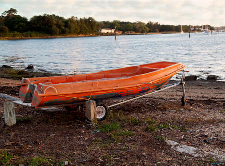 Colorful old orange boat tender on a trolley by a public slipway on a cloudy day.