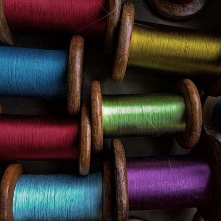 Vintage wooden spools with silk threads in a variety of colors including blue, red, green, yellow and purple.