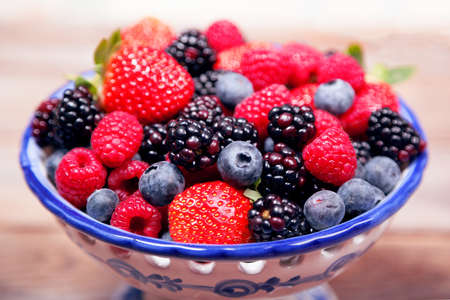 Mixed ripe sweet berries in a blue and white bowl  with shallow depth of field. Blueberries raspberries, strawberries and blackberries. With space for text. Imagens