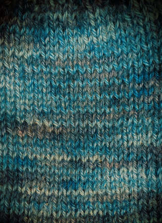 Handknitted background in various shades of blue with a vignette. Space for text. Imagens