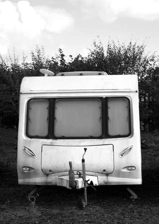 Black and white rundown dirty old caravan on a sunny day with clouds in the sky. Space for text. Imagens