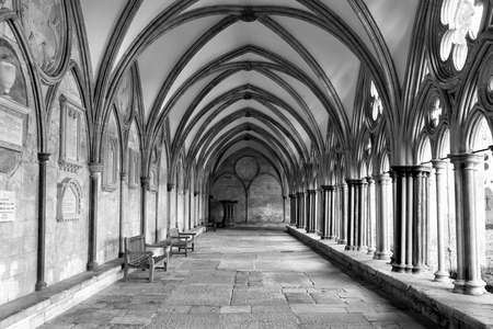 Black and White image of the external covered walkway of the Salisbury Cathedral Cloisters. An exterior walkway around the outside of the Cathedral.