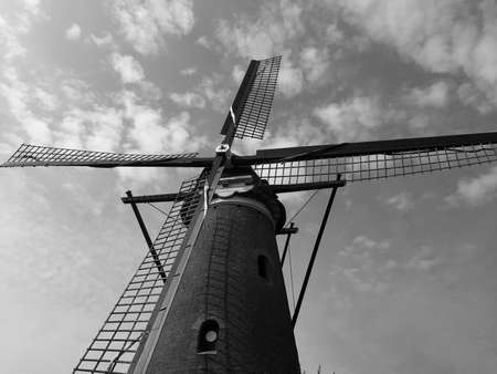 Black and white image of a windmill close up with clouds in the sky. Space for text. Imagens