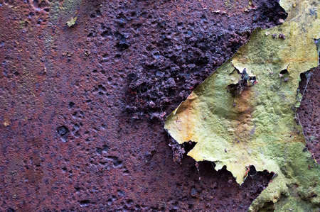 Rusty bumpy brown and purple textured background with green peeling paint with space for text. Imagens