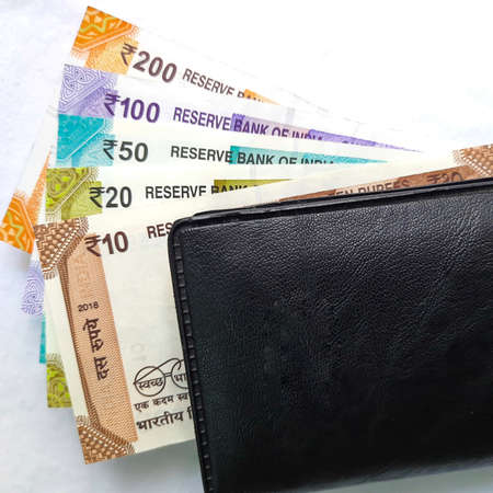 Indian new rupees currency notes arranged orderly number upwards manner with all rupee coins in white paper in wallet