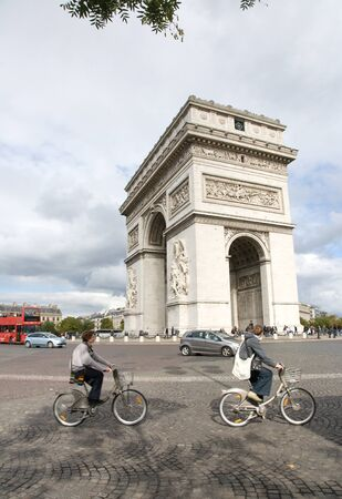 Paris, France - September 25, 2010: Tourist visiting Paris cycling around Paris most famous monument Arc de triumph
