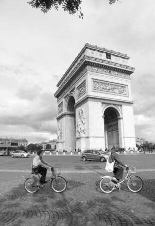 Paris, France - September 25, 2010: Tourist visiting Paris cycling around Paris most famous monument Arc de triumph