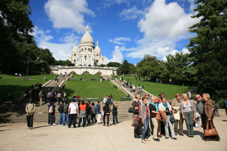 Paris, France, September 24, 2010 - A group of tourist taking group pictures in front of Basilica of the Sacre C��ur on bright sunny day.