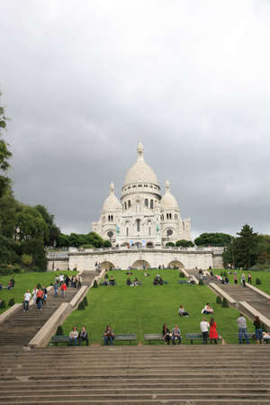 Paris, France, September 24, 2010 - Tourist relax themselves seating on the grass around Basilica of the Sacre C��ur on bright sunny day.