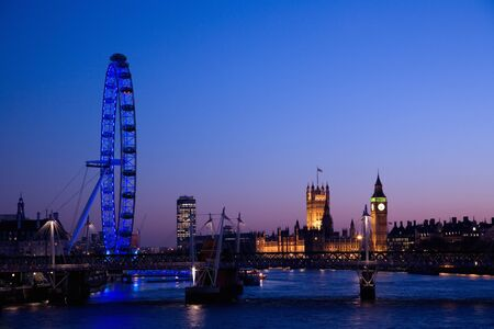 London, UK - March 7, 2011: London Eye and Westminster in the distance seen from Waterloo Bridge at dusk.