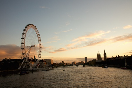 London, UK - November 6, 2010: London Eye and Westminster in the distance seen from Hungerford Bridge at dusk.