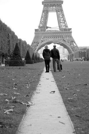 Paris, France - September 27, 2010: Couple tourist watching the Eiffel Tower in distance. This prominent tower was built in 1889 and is the most iconic symbol of Paris and France.