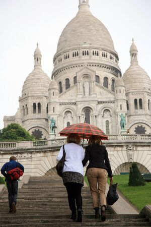 Paris, France, September 24, 2010- Tourist walk to Basilica of the Sacre C��ur with umbrella when start raining.