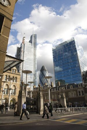 London, UK - September 16, 2010: Outside view of 30 St Mary Axe, likely being called Gherkin, and Heron Tower. Commuters walking pass by these modern buildings near Liverpool Street Station.  Stock Photo - 10164944