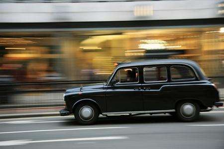 panning shot: Taxi in strada di Londra. Taxi, taxi, sono il simbolo pi� iconico di Londra e Londra