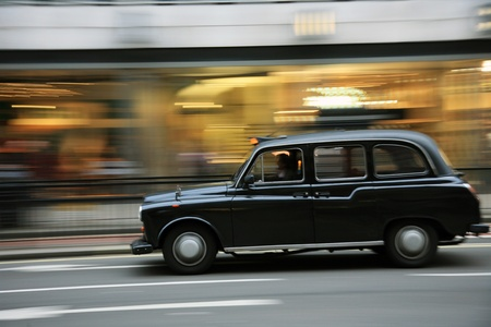 panning shot: Taxi in the street of London. Cabs, Taxis, are the most iconic symbol of London as well as London