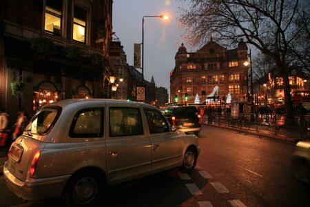London, UK - December 30, 2010: Taxi in the street of London. Cabs are the most iconic symbol of London as well as Londons Red Double Decker Bus.