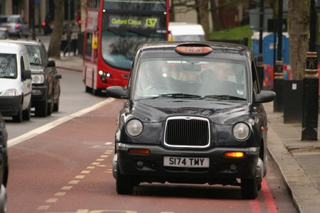 London, UK - April 01, 2010: Taxi in the street of London. Cabs are the most iconic symbol of London as well as London Stock Photo - 10321657
