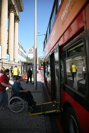 carers: London, UK - May 25, 2011: Man in a wheelchair getting on a public bus with carers help