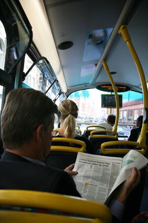 London, UK - August 09, 2010: One bus passenger reads news paper seating on upper deck.      Stock Photo - 10404632