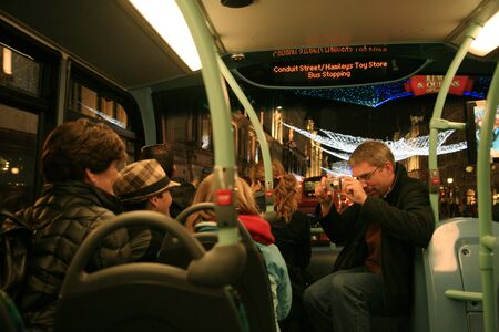 christmas ground: London, UK - November 21, 2010: Group of family visitors seating on a bus taking photos in the back ground of Street Night View of Regend Street with Christmas Decoration. Regend Street is one of the most famous shopping street in London and also famous f