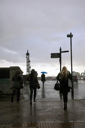 sudden: London, UK - December 19, 2010: People start running to escape from sudden storm around Hampton Court Bridge in London.