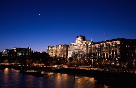 river scape: London Victoria Embankment Night View seen from Waterloo Bridge - Embankment Place, Adelphi Terrace and Shell Mex House from Left
