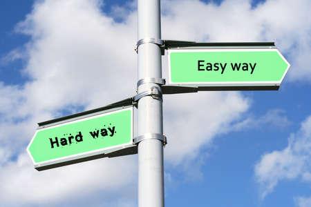 hard way: Street post with Easy way, Hard way signs.  Stock Photo