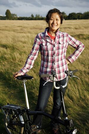 Woman in Richmond Park with bicycle at dusk    photo