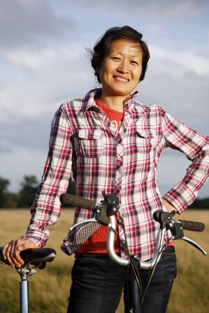 korean woman: Woman in Richmond Park with bicycle at dusk    Stock Photo
