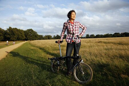 Oriental woman in Richmond Park with bicycle at dusk  photo