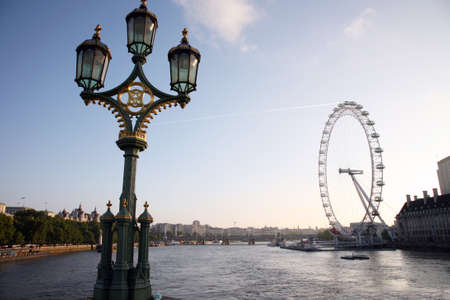 London, UK - June 03, 2011: An old style street lamp in Westminster Bridge and Millennium Wheel over Thames River.