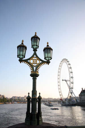 millennium wheel: London, UK - June 03, 2011: An old style street lamp in Westminster Bridge and Millennium Wheel over Thames River.