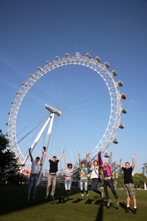 millennium wheel: London, UK - June 03, 2011: Group of young tourist give pose, jump up, London Eye in the back ground.