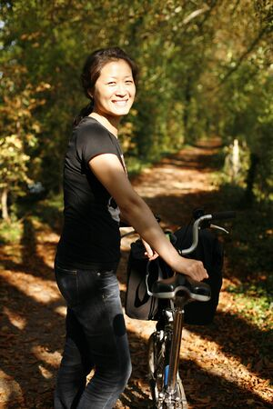 Woman with bicycle in a park, autumn   photo